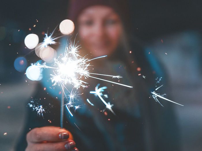 Close-up of woman holding sparkler burning at night