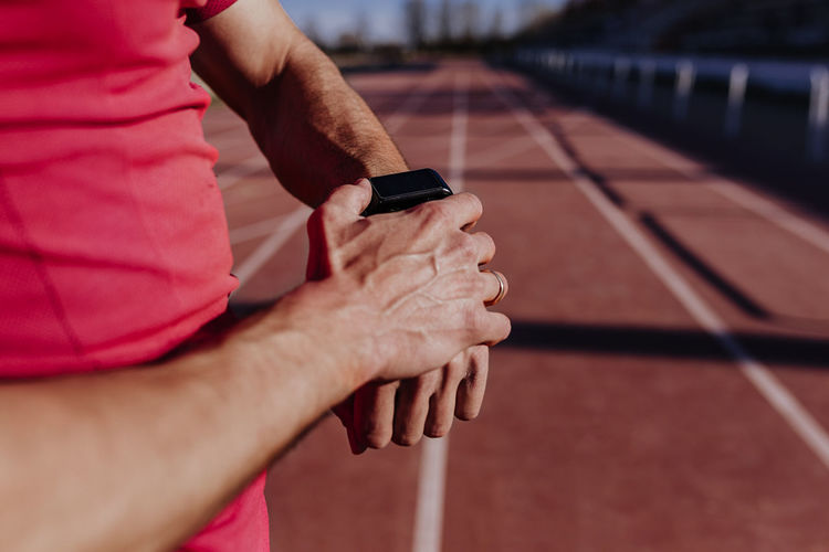 Midsection of athlete wearing smart watch on sports track