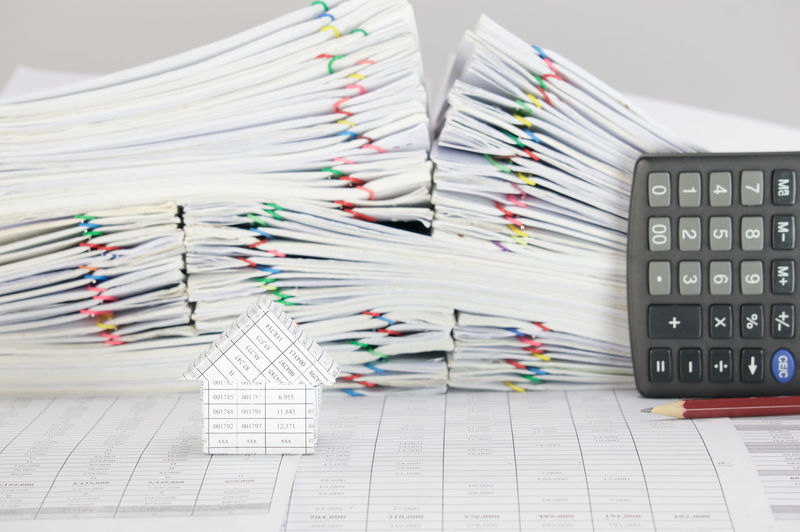 Close-up of model house with pencil and calculator by stacked files against gray background