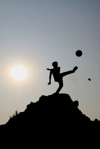 Low angle view of silhouette boy playing with ball against sky during sunset