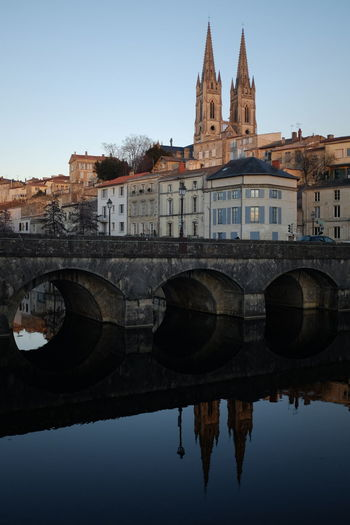 Arch bridge over river with reflection of buildings against sky in town