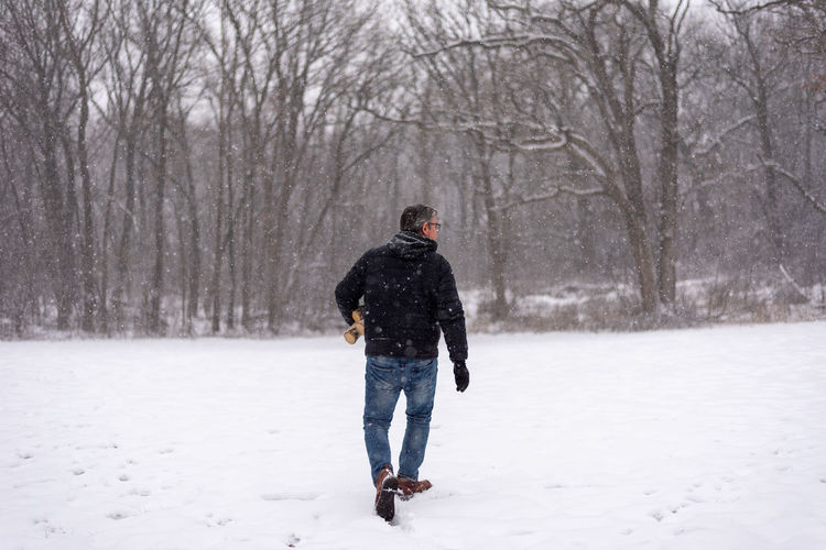 Rear view of man walking on snow covered land against trees