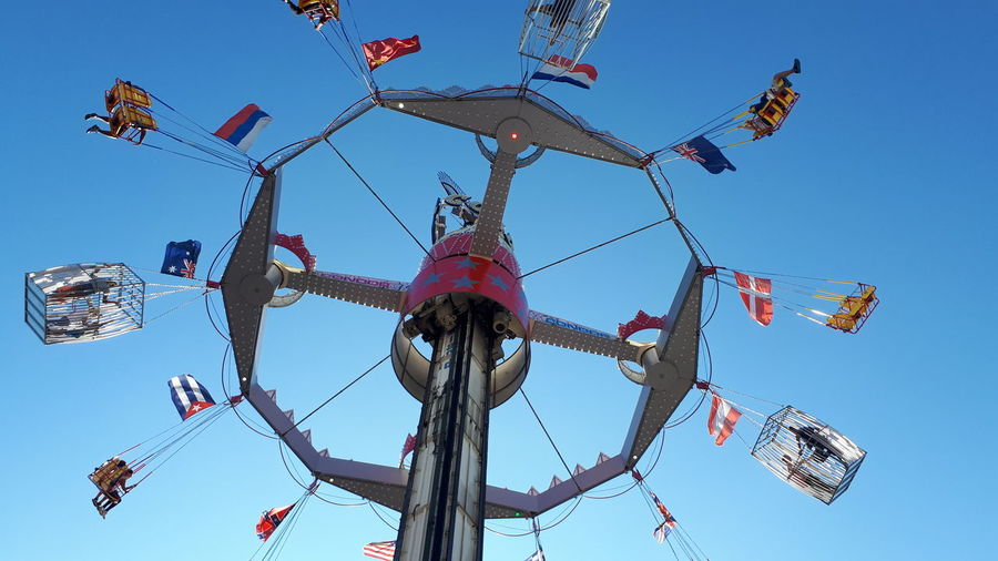Low Angle View Of Chain Swing Ride Against Clear Sky