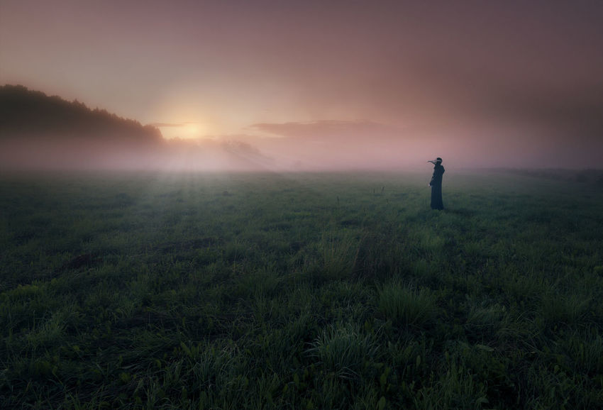 Fine Art Photography Finland Misty Beauty In Nature Colorful Field Fog Grass Landscape Mood Mystical Nature One Person Outdoors People Plague Doctor Real People Sky Standing Sun Sunset Tranquility