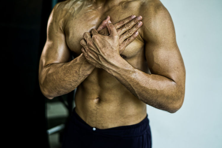 Midsection of shirtless man with hand on chest