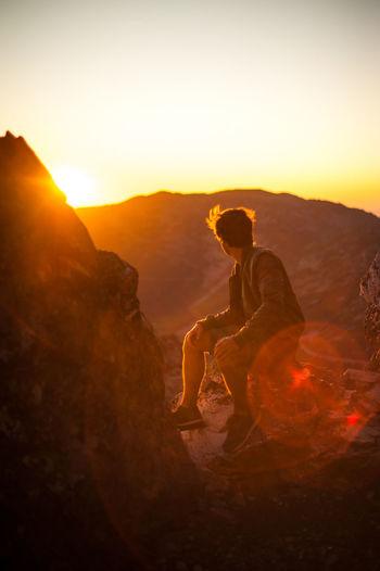 Full length of man sitting on rock against sky during sunset