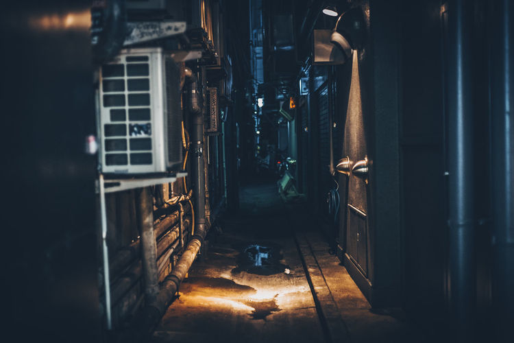 Alley amidst buildings at night