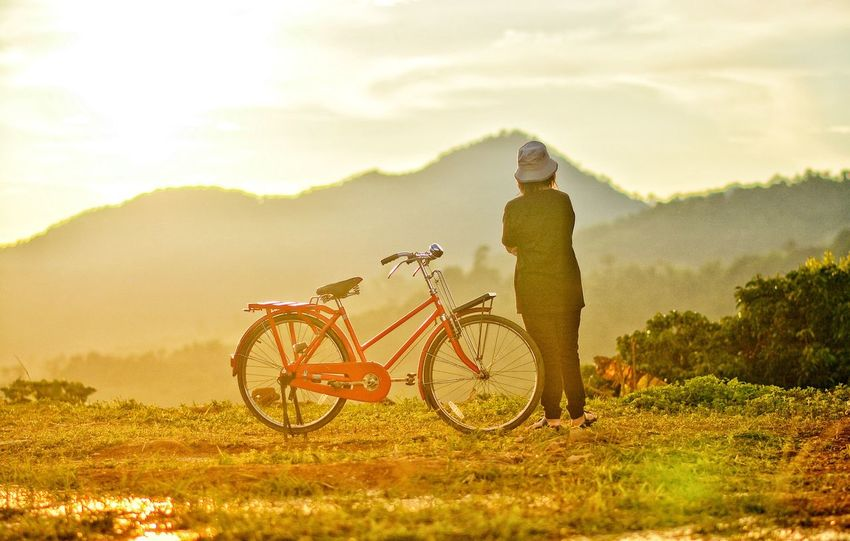 Bicycle Transportation One Person Mode Of Transportation Sky Real People Lifestyles Plant Nature Cloud - Sky Leisure Activity Sunlight Land Vehicle Field Full Length Activity Beauty In Nature Cycling