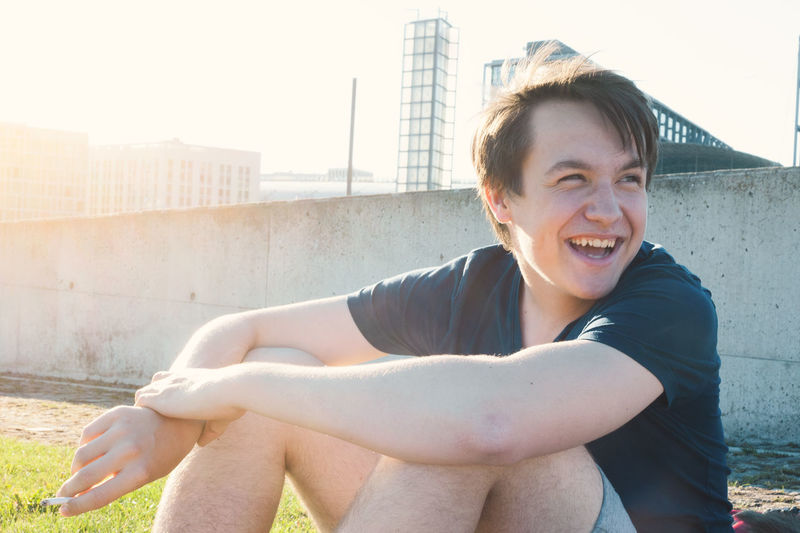 Smiling young man sitting on city against sky