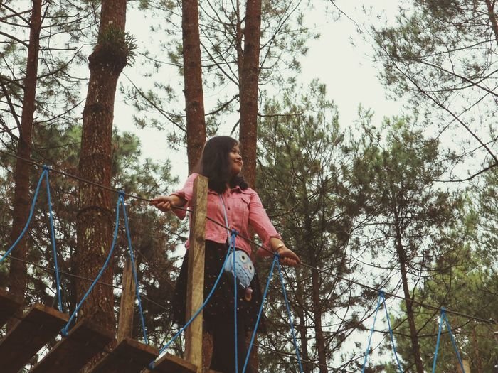 Low angle view of woman standing against trees in forest