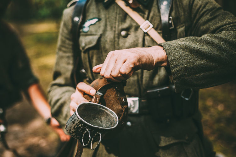 Midsection of army soldier holding bottle and mug while standing in forest