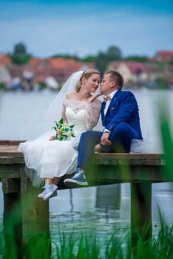 Romantic bride and groom sitting on wooden pier over lake