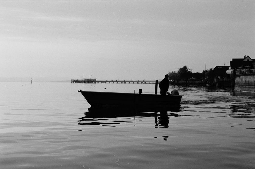 Fisherman Leaving the Harbor in the Sunset. Water Silhouette One Man Only One Person Reflection Nautical Vessel Standing Adult Lakeconstance Lake Constance Bodenseeregion Blackandwhite Film Photography Analog Photography Analogue Photography Filmisnotdead EyeEmNewHere