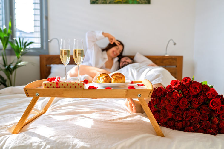 Midsection of woman having food on bed at home
