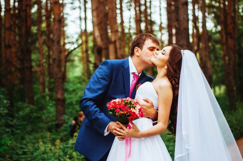 Bridegroom kissing bride against trees in forest