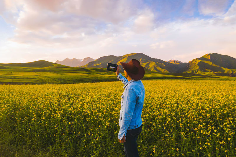 Man photographing while standing amidst flowering plants on field