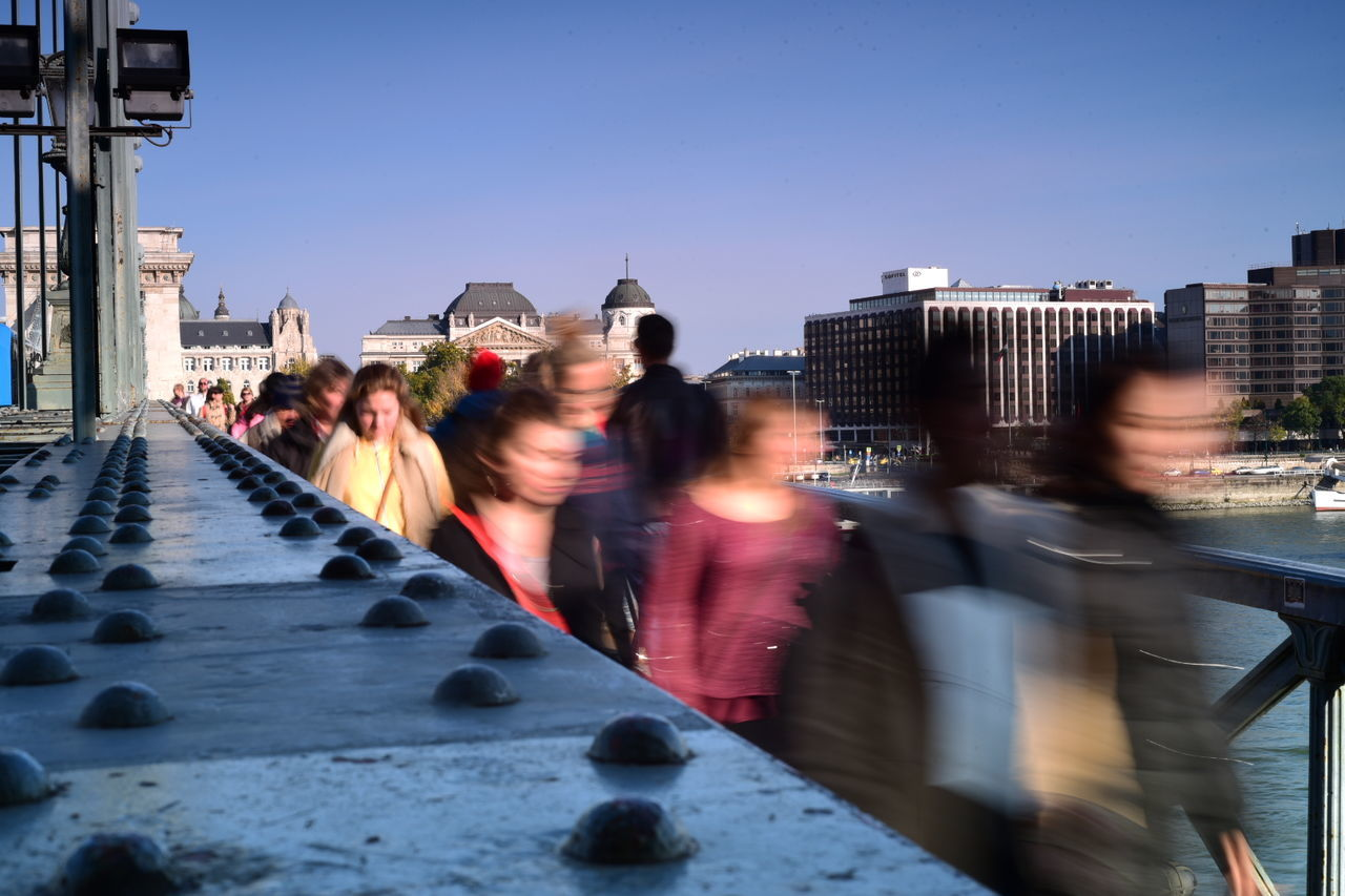 blurred motion, architecture, built structure, building exterior, real people, transportation, motion, day, city, large group of people, outdoors, men, sky, people