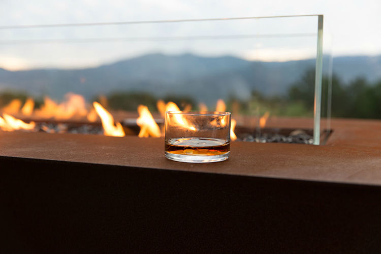 Close-up of lit candles on table against sky during sunset