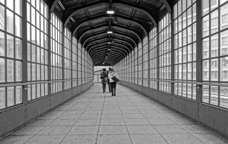 Rear view of people walking through passage