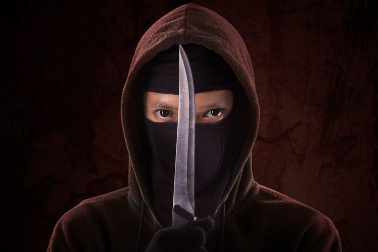 Portrait of man holding knife against wall