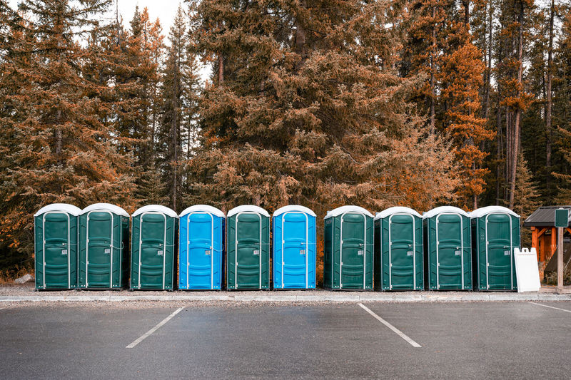 Portable toilets by road against trees during autumn