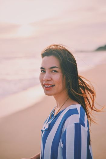 Side view portrait of smiling young woman standing at beach during sunset