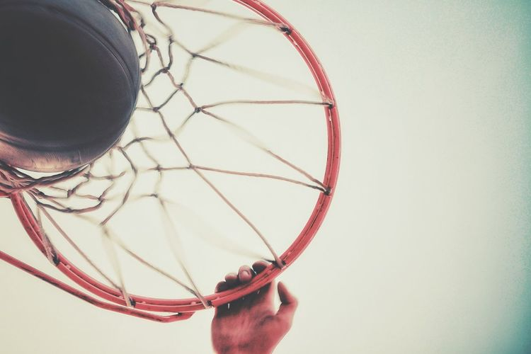 Cropped hand of man holding basketball hoop against clear sky