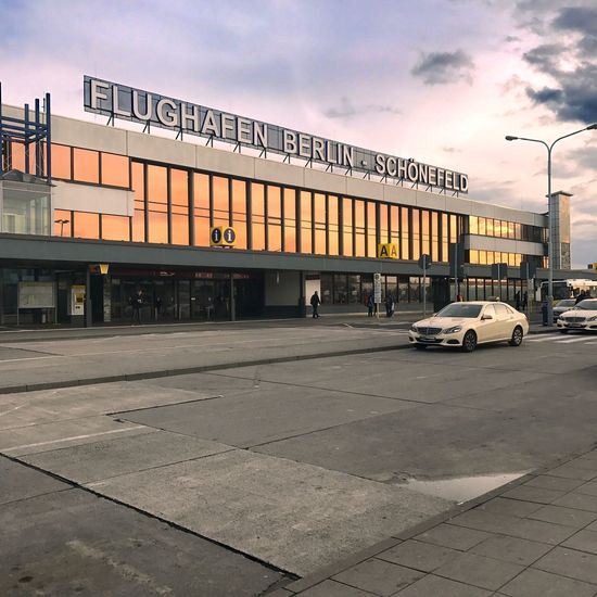 Transportation Architecture Text Building Exterior Car Built Structure Outdoors Communication Sky City Land Vehicle Sunset Travel Destinations Day No People Airport Berlin Schönefeld Airport