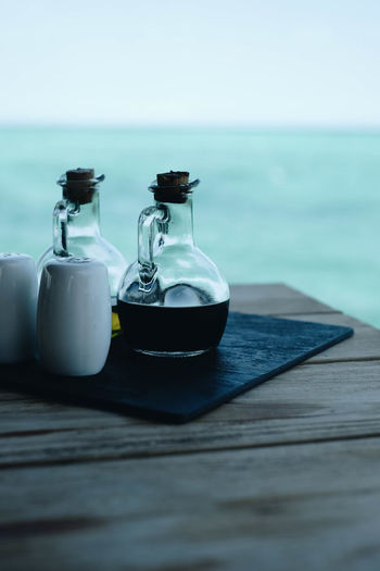 Close-up of coffee on table by sea
