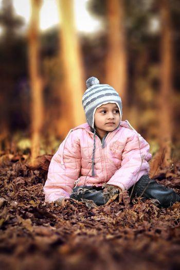 Cute girl in warm clothing sitting on field