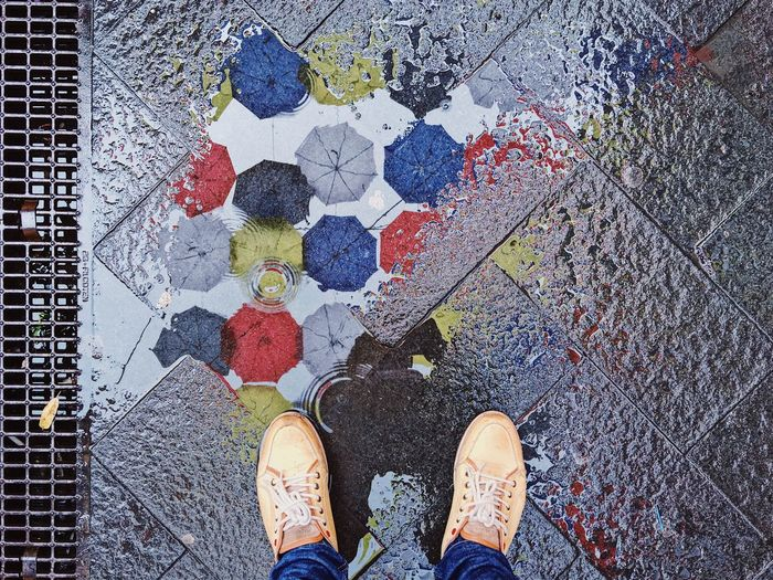Low Section Of Man Standing By Puddle With Umbrellas Reflection On Footpath