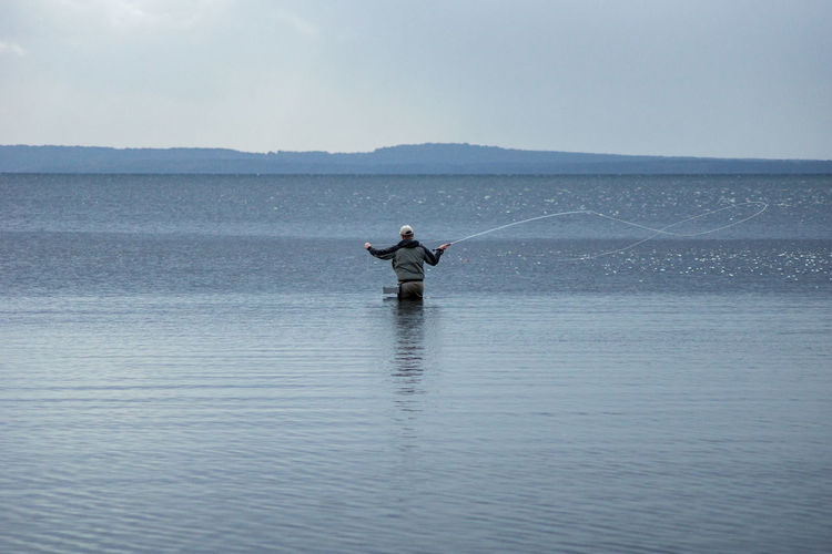 Rear View Of Man Fishing In The Ocean