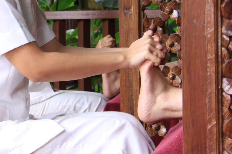 Midsection of woman massaging leg at spa