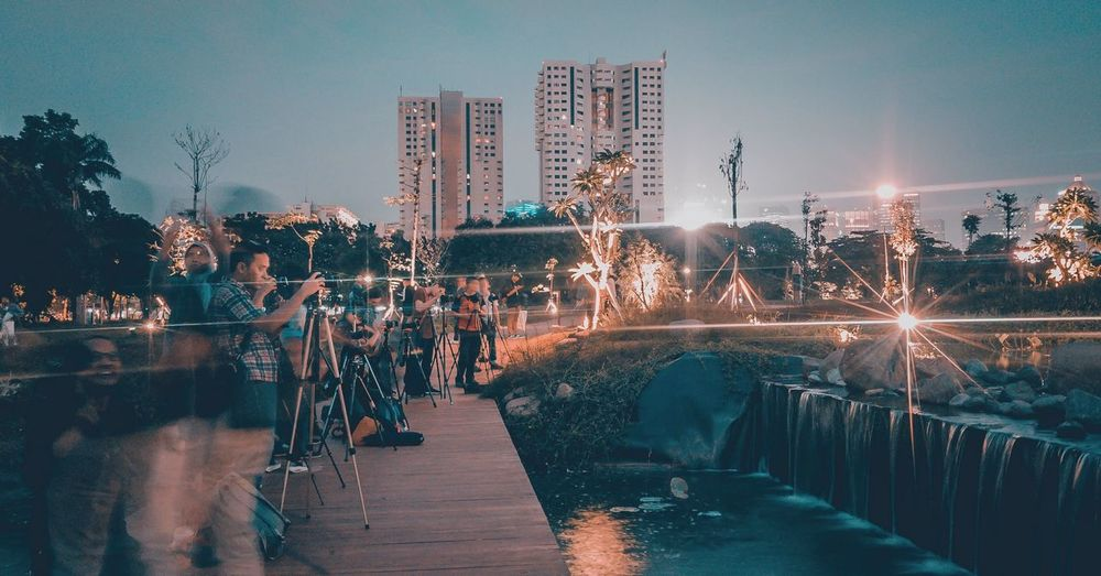 People photographing waterfall in city at night