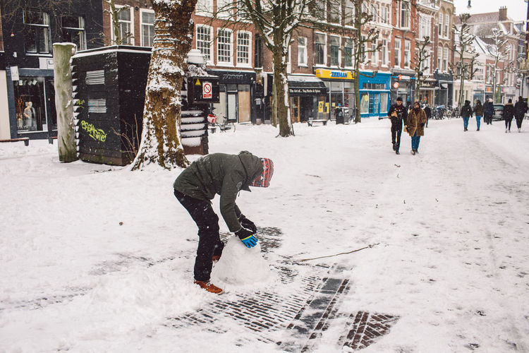 Man walking on snow covered street during winter