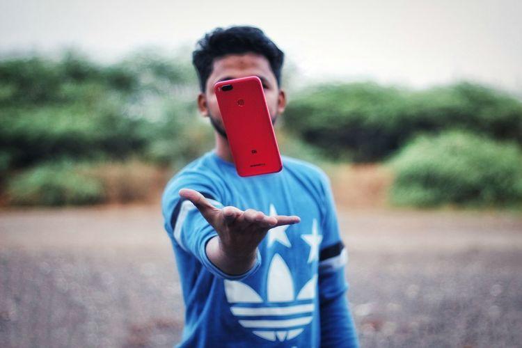 Full length of boy using mobile phone outdoors