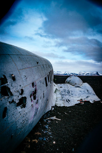 Abandoned military airplane at beach against cloudy sky during winter