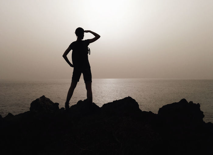 Silhouette woman standing on rock by sea against clear sky
