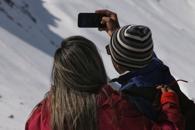 Couple taking selfie with smart phone while standing outdoors during winter