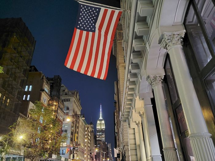 Low angle view of illuminated flag amidst buildings in city at night