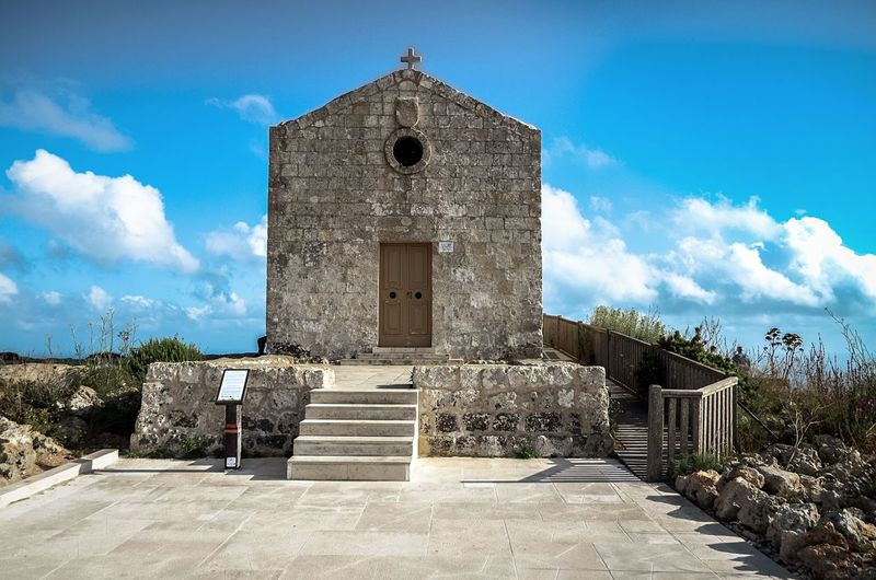 The place speaks of sanctity. A chapel of the cliffs, built in 1646. St. Mary Magdalene Chapel Dingli Dingli Cliffs Malta Architecture Clouds Sky Building Exterior No People Place Of Worship Religion Catholic Travel Frontage Front View Blue Wave Church Religious Architecture Religious  Summer