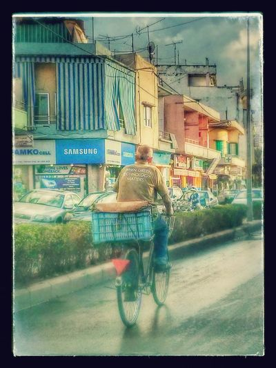 Old man on a Bicycle wearing an Environmental t-shit The Environmentalist – 2014 EyeEm Awards