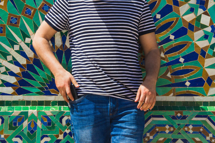 Moroccan Adult Blue Casual Clothing Communication Floral Pattern Front View Human Body Part Indoors  Jeans Leisure Activity Lifestyles Men Midsection Multi Colored One Person Pattern PhonePhotography Real People Smart Phone Standing Striped Style Wall - Building Feature Young Adult