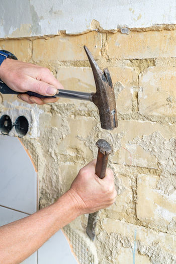 Worker hammering old wall
