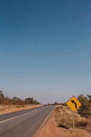 Arrow sign on road against clear blue sky