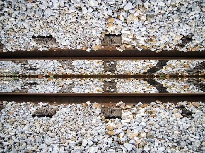 High angle view of railroad track and gravels on field