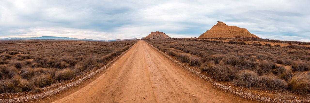 Panoramic shot of dirt road amidst land against sky