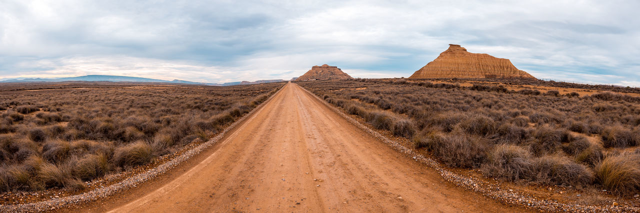 Panoramic shot of dirt road amidst land against sky