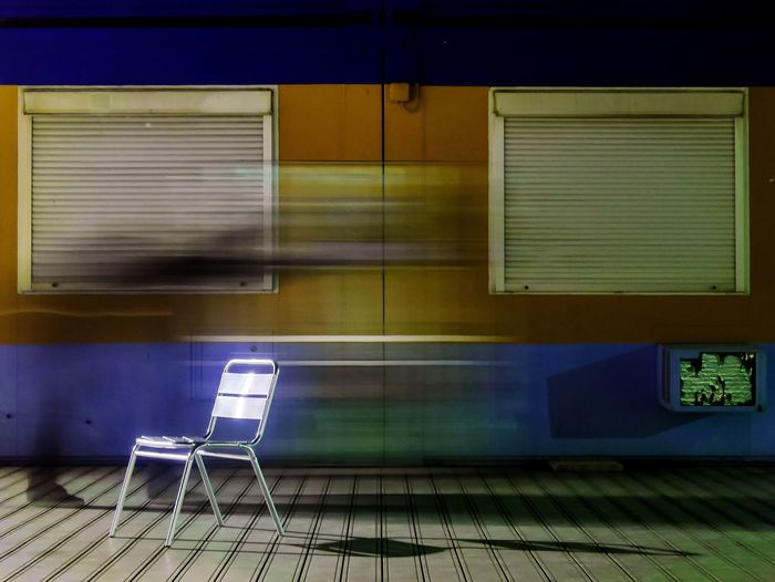 Blur image of person walking next to chair on footpath