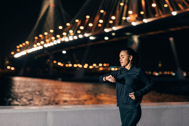 Young woman standing on bridge at night